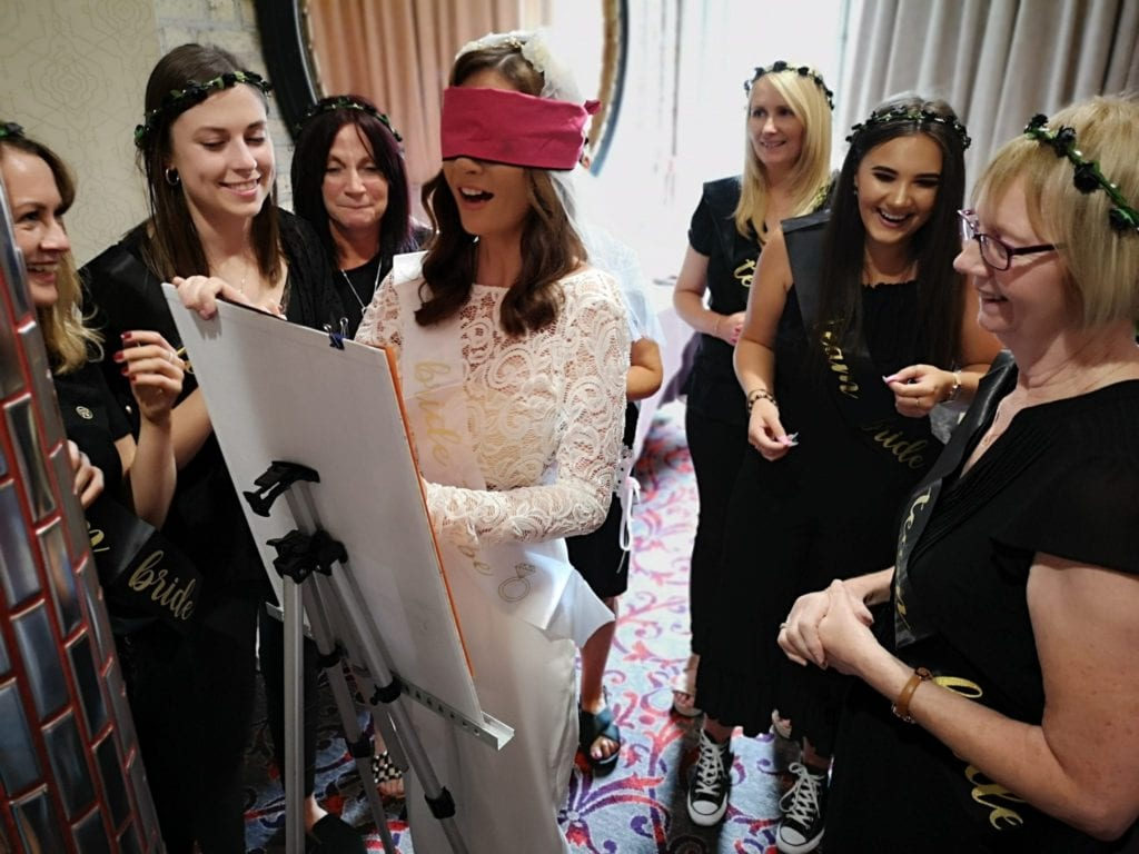 Bride to be in a white dress with a pink blindfold surrounded by her friends at a hen party activity
