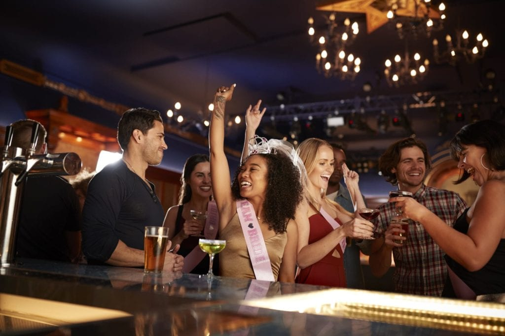 Group Of Dancing Friends Celebrating With Bride On Hen Party In Bar