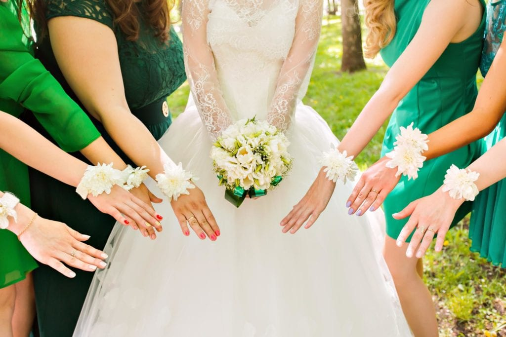 Bride and bridesmaids hold hands