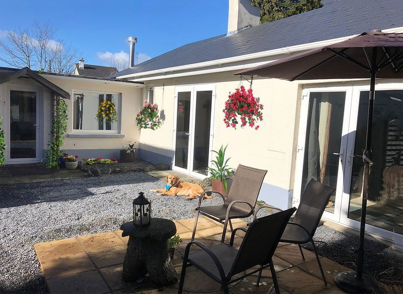 Cream Bungalow with double doors dog outside with blue bandana flowers stone area with seats table and candle under sun parasol