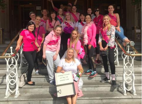 hen party group of girls in pink sashes, bride to be holding champagne bottle