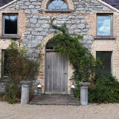 a door and 3 windows on the outside of the hen party house the stables