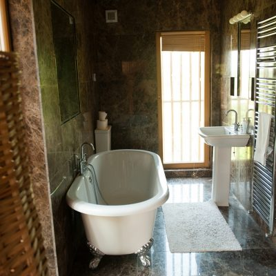 Long bathroom with roll top bath with silver feet, marble tiles, full long windows, mirrors
