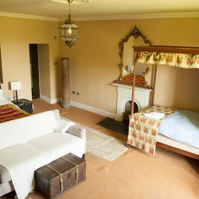 Large bedroom with cream walls and cream carpet, four poster bed with patterned linen, second double bed with cream couch and wooden trunk, fire place mirror, antique light fittings in bishopstown house large hen party self catering