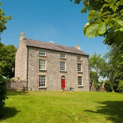 Large stone house with french windows and red front door green lawn trees bird table at Bishopstown self catering house for a large hen party