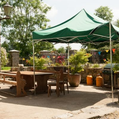 Outside area with wooden benches and chairs, green gazebo, potted plants, coloured bunting, green trees, stone walls at bishopstown hen party house