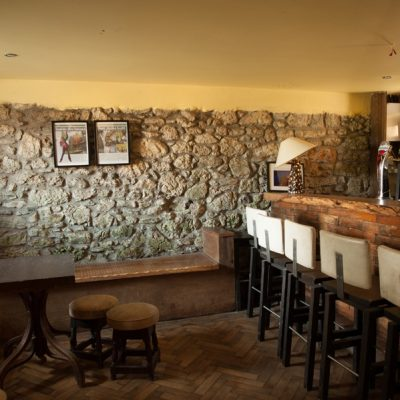 Wooden Bar with Guinness taps stone walls old style posters bar stools benches tables wooden lamp in bishopstown house hen party house in Ireland