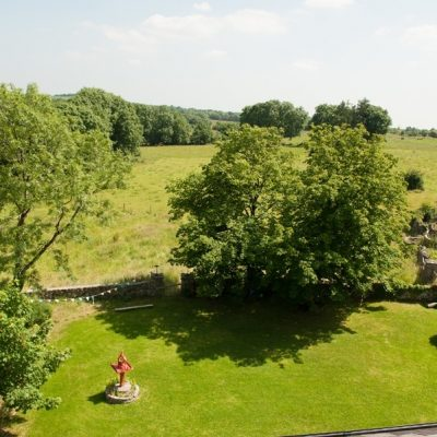 Rooftop view of the beautiful garden with red bird table large green lawn oak trees stone walls colourful bunting and farm animals and trees in the distance in bishopstown house self catering house for large hen party in Ireland