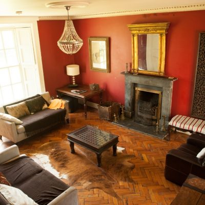 Large sitting room with stone fireplace gold mirror wall features and artwork comfy couches and benches coffee table with animal rug wooden floor in Bishopstown house a large self catering house for a hen weekend