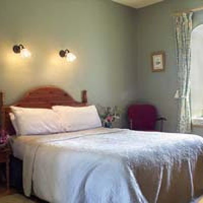 Spacious green bedroom with large wooden bed, white bedspread and pillows, fresh flowers, patterned tie back curtains, window seat, french windows, wooden floor in blanchville selfcatering house in kilkenny