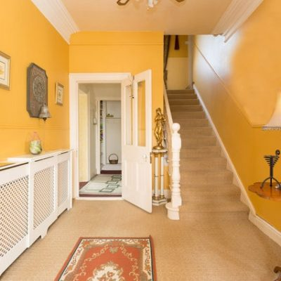 Yellow Hallway with grand staircase in Galway Banba House