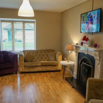 sitting room with open fire & couches in Carlingford