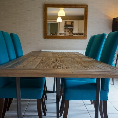 Dining room table & blue chairs with large wall mirror
