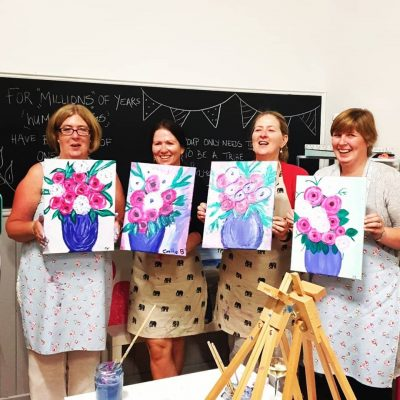 4 Ladies holding up paintings from a Sip & Paint activity