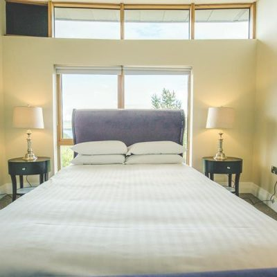 Large double bed with purple headboard set against a sea view backdrop