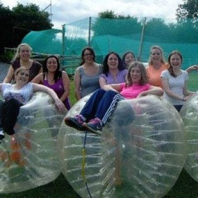 Girls sitting in and standing around large bubble soccor balls